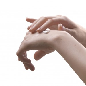 isolated image girl applying white cream to hands